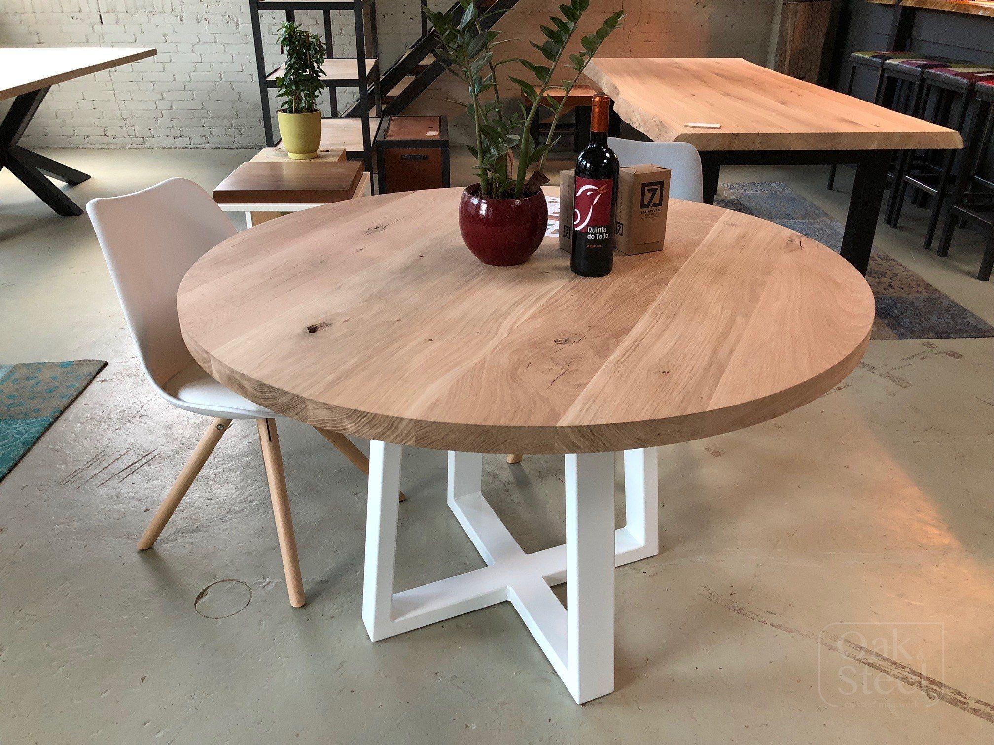 Ronde eiken tafel van 4 cm dik. Op een wit onderstel